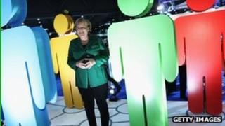 German Chancellor Angela Merkel stands among coloured figures at a CPU meeting in Leipzig. Photo: 15 November 2011