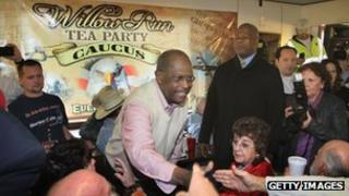 Herman Cain shakes hands at a Tea Party rally