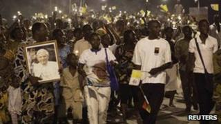 "Worshippers carry oil lanterns and dance during a night time procession through the streets of Benin""s main city of Cotonou, 17 November 2011"