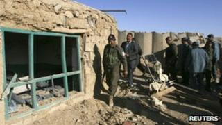 Afghan officials inspect the police post where the clash happened
