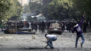 Protesters throw stones at riot police near Tahrir Square 21 November 2011