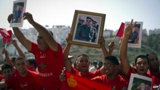 Moroccans hold up portraits of King Mohammed VI along a road in Tangiers 29 September 29, 2011.