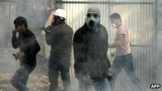 Egyptian protesters use masks to protect themselves from tear gas on 23 November