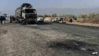 (File photo) Afghan policemen and locals watch a burned out fuel truck, supplying a US-run base, after being targeted by a bomb near Bagram air base some 50, kms north of Kabul on October 26, 2011.