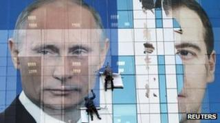 Workers attach an election poster featuring Russia's President Dmitry Medvedev (R) and Prime Minister Vladimir Putin, appealing to people to vote for the United Russia political party in 4 December parliamentary elections, onto an office building in the southern city of Krasnodar on Thursday