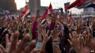 Egyptian protesters raise their hands during a mass rally demanding an end to military rule at Tahrir Square in Cairo on November 25, 2011