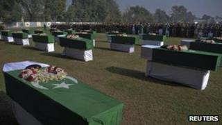 Pakistan's national flags cover the caskets of soldiers killed in a cross-border attack along the Pakistan-Afghan border during their funeral prayers