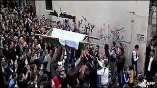 An image grab taken from a video uploaded on YouTube shows Syrian mourners carrying the coffin of a victim killed in recent violence in Tal Kalakh in the Homs governorate