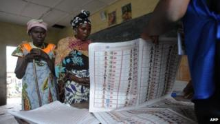 Congolese women wait to recive ballot papers at a polling station in Goma during the presidential and legislative elections November 28, 2011.