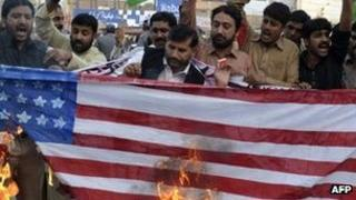Supporters of the Pakistan Muslim League-Nawaz (PML-N) party burn a US flag during a protest in Multan on November 28, 2011, against a Nato strike on Pakistan troops.