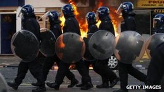 Line of police officers in riot gear walking past a burning car in Hackney on August 8 2011 in London