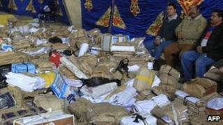 Election workers sit next to stacks of unopened ballot papers at a counting centre in Cairo, 30 November 2011