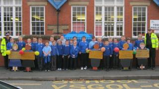 Pupils with the wooden pupils outside Ysgol y Maelgwn