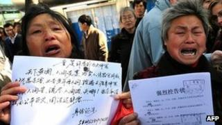 Agitated Chinese petitioners show documents during a gathering outside a courthouse in Beijing