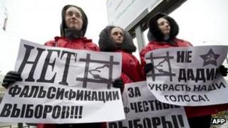 """Communist Party activists in Moscow hold posters saying """"No to vote-rigging"""", 2 December"""