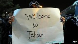 An Iranian student holds a banner to welcome the return of expelled Iranian diplomats from London (2 Dec 2011)