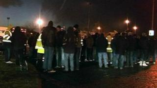 Men standing outside an oil refinery