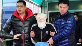A fishing captain suspected of murdering a South Korean coast guard is taken by South Korean maritime police at a hospital in Incheon, west of Seoul, on December 12, 2011.