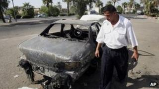 An Iraqi traffic policeman inspects a car destroyed by a Blackwater security detail in Baghdad, Iraq (September 2007)