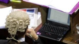 Barrister with laptop in courtroom