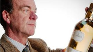 A Bonham's auctioneer inspects the bottle of Glenfiddich whisky