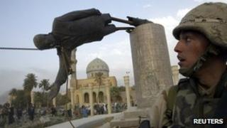 US Marine Kirk Dalrymple watches as a statue of Iraq's President Saddam Hussein falls 9 April 2003