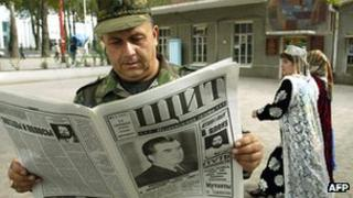 Tajik officer reads newspaper