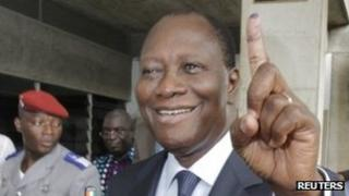 Ivory Coast's President Alassane Ouattara displays his inked stained finger after casting a ballot at a polling station in Cocody, December 11, 2011.