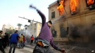 An Egyptian protester hurls a stone at security forces as a building burns in Cairo, 18 December