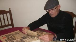 Tony Oliver reads newspaper cuttings about his brother's murder