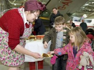 Cook giving children wartime-recipe cake