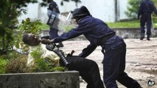 A police officer grabs a supporter of Etienne Tshisekedi in Kinshasa, DR Congo (8 Dec 2011)