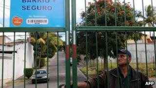 A security guard closes a gate installed in a street of Tres Caminos neighbourhood in Tegucigalpa, on 19 December 2011