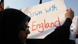 A protester holds a poster displaying the message 'Down with England' in Tehran