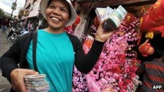 A lady carrying Indonesian rupiahs