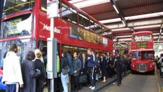 People queue for a bus