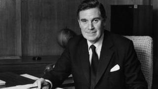 Sir Ian Trethowan sitting at a desk.