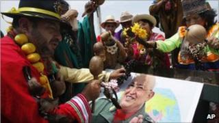 Peruvian shamans perform a good luck ritual over a picture of Venezuelan leader Hugo Chavez
