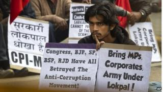 An activist of Communist Party of India (Marxist and Leninist) listens to a leader during a protest against the government's version of an anti-corruption bill in New Delhi, India, Thursday, Dec. 29, 2011