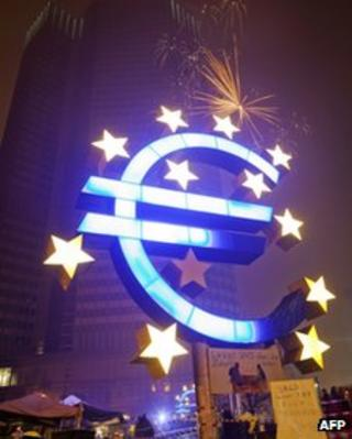 A single firework explodes above the euro sculpture in front of the European Central Bank in Frankfurt