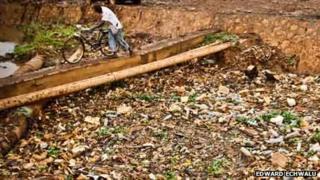 A man in Uganda's capital, Kampala, pushes his bike over a drainage channel clogged with rubbish (Photo: Edward Echwalu)