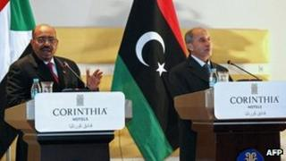 """Sudanese President Omar al-Bashir (L) speaks during a news conference with Libya's National Transitional Council""""s chief, Mustafa Abdel Jalil (R) in Tripoli on 7 January 2012"""