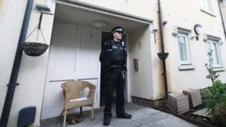 Police officer outside murdered man's house