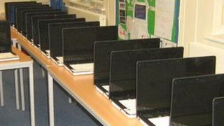Laptop computers lined up on school desks