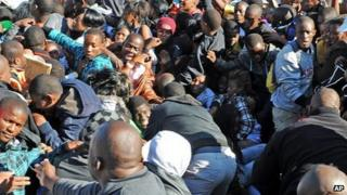 Thousands of young students and their parents push their way into the gates causing a stampede at the University of Johannesburg, South Africa, Tuesday 10 January 2012