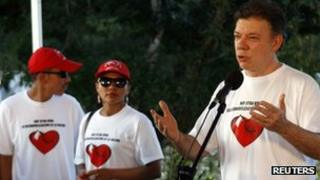 "President Juan Manuel Santos speaks next to two demobilised rebels during ""Operation Rivers of Light"" on 21 December 2011"