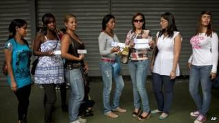 Women affected by breast implants made by the defunct French brand Poly Implant Prothese, PIP, show their breast implants certificate to journalists outside the civil court in Caracas, Venezuela, on 6 January 2012
