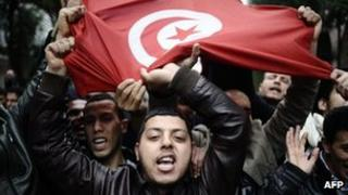 Demonstrator holds a Tunisian flag during a protest in Tunis on 18 January , 2011, amid the uprising which led to the overthrow of the dictatorship of Zine al-Abidine Ben Ali