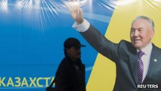 A man in Almaty walks by an election poster of the Nur Otan party led by President Nursultan Nazarbayev. Photo: January 2012