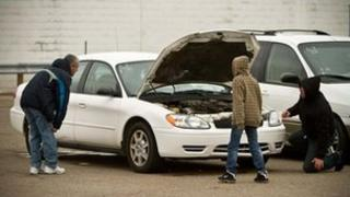Potential buyers check out a used car at the Detroit auction